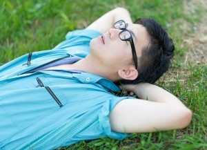 芝生の上で眠る人